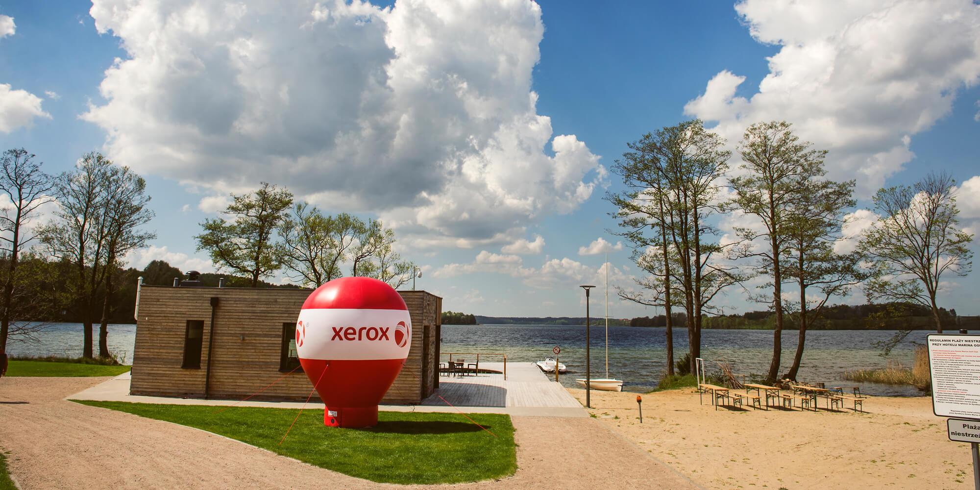 Balo reklamowy z brandingiem Xerox stoi nad jeziorem